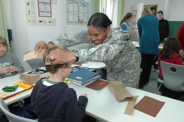 U.S. Army Garrison Heidelberg Command Sgt. Maj. Annette Weber helps a student at the Englisches Institut in Heidelberg during a community relations project in November.
