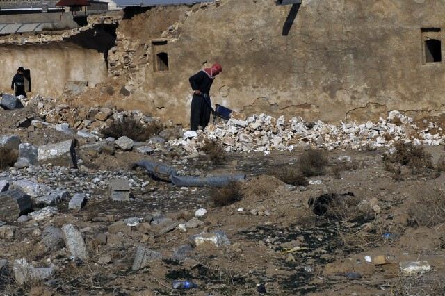 An Iraqi man works to pick up the rubble left inside the Kirkuk Citadel, where Kurdish and Turkomen families once inhabited the ancient houses inside.
