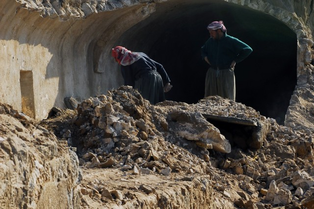 Two Iraqis work to clean up the rubble left behind at the Kirkuk Citadel, in Iraq. This is one of many efforts launched in the province to refurbish historical sites.