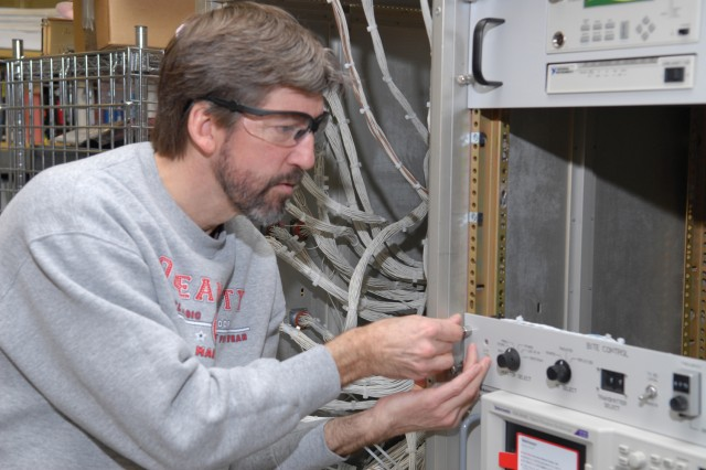 Bill Dierolf, electronics mechanic, installs a control panel for the MUTES built-in test equipment.