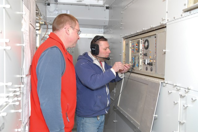 Electronics mechanic Dave Levandoski, left, and Jeff Kramer, crew chief, complete final adjustments and alignments to a transmitter.