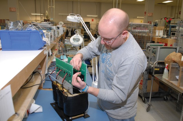 Jeff Ackerman, electronics mechanic, completes the mechanical buildup of a 250 volt power supply.