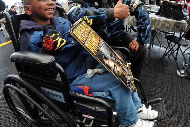 U.S. Army Top Fuel dragster driver Tony Schumacher gives a thumbs up to Jalen Smith, 7, of Rialto, Calif., during a rain delay Feb. 7 at the NHRA Kragen O'Reilly Auto Parts Winternationals at Auto Club Raceway in Pomona, Calif.