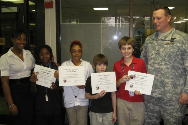 Fort Polk Garrison Commander Col. David Sage and Tammy Williams, teen program coordinator, congratulate the first group of teens to graduate from Fort Polk's Army Family Team Building teen program. From left are Williams, Taliyah Rambert, Ashley Toombs, David Matson, Dylan Hager and Sage.