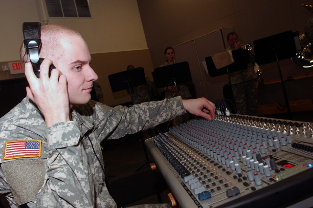 Spc. Doug Wurtele, a flute player assigned to the 100th Army Band, listens to various inputs on the sound board during the rock band rehearsal held at Fort Knox, Ky. The unit's rock band is one of three musical support teams that perform numerous performances year round.