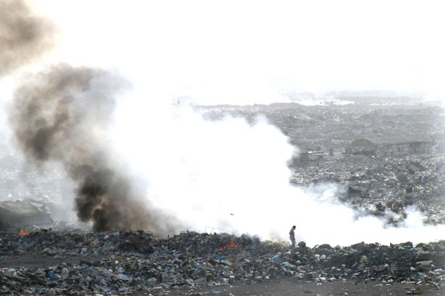 An Iraqi man makes room for more debris by burning the garbage to compact one of the local landfills in Baghdad Feb 7.  The 890th Engineer Battalion, 926th Engineer Brigade, Multi-National Division - Baghdad, conducts route clearance and sanitation patrols to clear Iraqi communities of debris and deny terrorists the ability to hid improvised explosive devices.