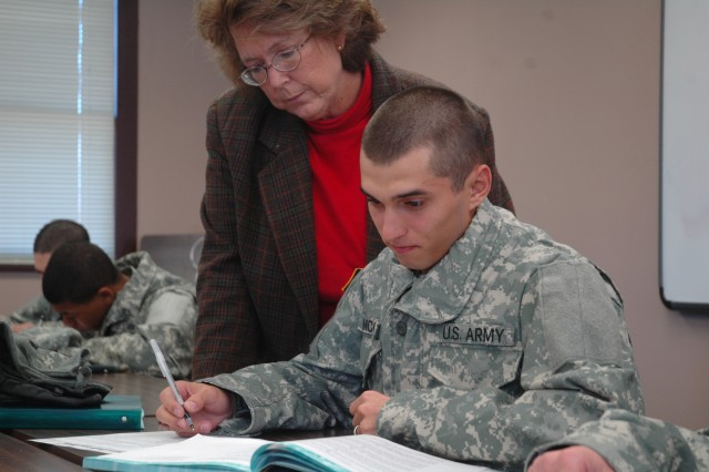 Pvt. Preston McCord, a Soldier at the U.S. Army Preparatory School, receives help from his reading and writing instructor, Holly Moore.