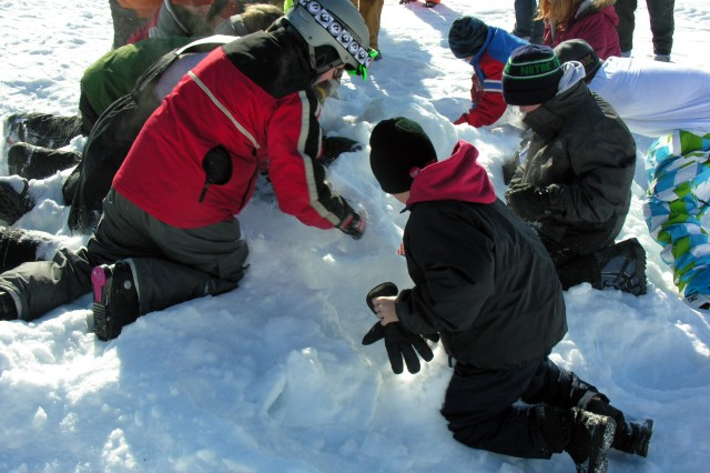 """Youths dig through the Snow Dig Pile at the Winter Extravaganza at the Fort McCoy Whitetail Ridge Ski Area. The new event proved to be popular as youths searched through the snow for coins and other valuable prizes."""""""