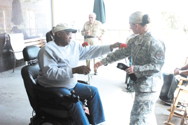 Staff Sergeant Michelle Duncan gives a carnation to Windell McClain at the Georgia War Veterans' Home for Valentine's Day, Feb. 9 in Milledgeville, Ga.