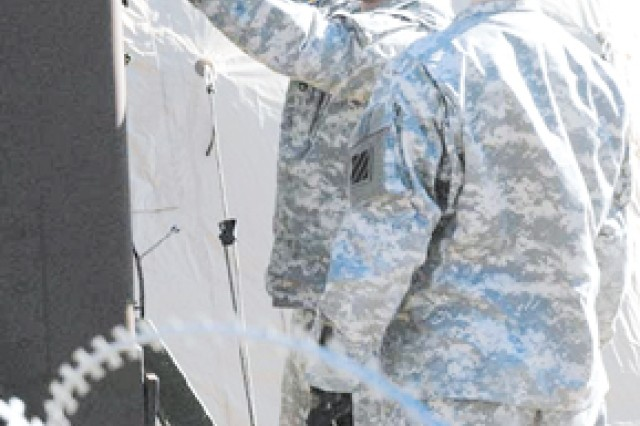 Staff Sergeant Edward J. Nowicki, left, and Spc. Joshua Thomason, both from HHT, 3rd HBCT, examine connections to some of the Fusion Cell's equipment during a Fusion Cell field exercise, Feb. 4 on Kelley Hill at Fort Benning.