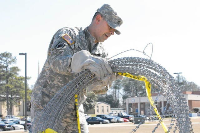 Intelligence exercise completes - Staff Sgt. Edward J. Nowicki, noncommissioned officer in charge of the 3rd Heavy Brigade Combat Team's Fusion Cell and member of Headquarters and Headquarters Troop, 3rd HBCT, 3rd Infantry Division, helps break down concertina wire after a Fusion Cell field exercise, Feb. 6 on Kelley Hill at Fort Benning.  The exercise, which was conducted Feb. 2 - 6, demonstrated the unit's intelligence gathering capabilities.
