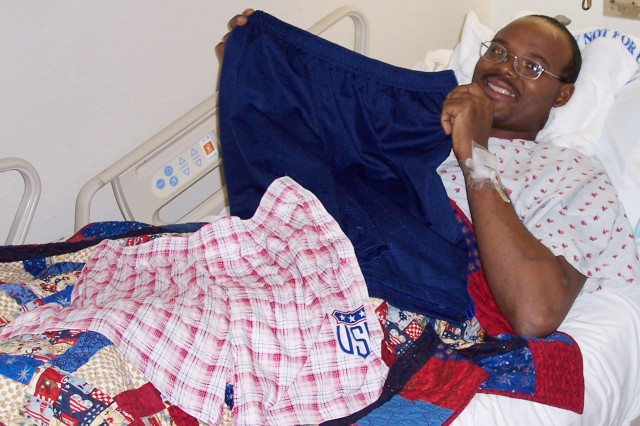 A servicemember holds up a pair of Sew Much Comfort adaptive shorts while he recovers at Germany's Landstuhl Regional Medical Center. The troop-support group provides adaptive clothing free of charge to support the unique needs of injured