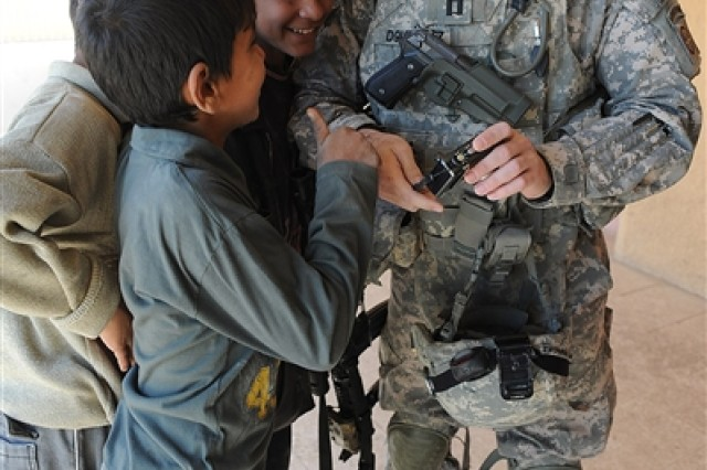 Army Capt. Agustin Dominguez shows Iraqi children his camera after taking a picture of them during a humanitarian mission in eastern Baghdad's New Baghdad district Feb. 4, 2009. U.S. soldiers and Iraqi National Police distributed more than 800 wool blankets to New Baghdad residents.