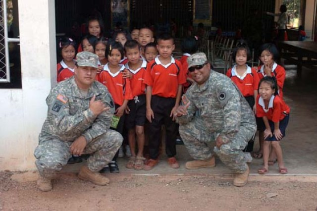 Spc. Andrew Kalaukoa (right) and Spc. William Cook pause for a quick picture with the children of the Ban Soi Song School before distributing cases of milk to the schoolchildren.  Kaluakoa and Cook are on a team as part of the Cobra Gold joint humanitarian mission hosted at the Ban Nong Buatong School in the Chanthaburi District of Thailand Jan. 24 to Feb. 11.