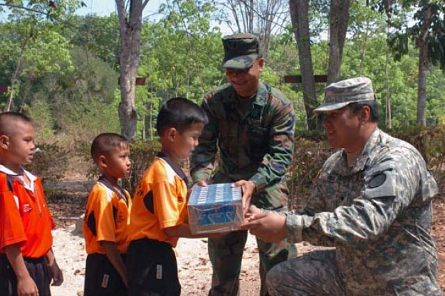 Spc. William Cook (right) and Thai Marine Petty Officer Prawet Asasoy (left) distribute milk to the children of the Ban Pra Gad School in rural Thailand as part of the Cobra Gold joint humanitarian mission hosted at the Ban Nong Buatong School in the Chanthaburi District of Thailand Jan. 24 to Feb. 11.