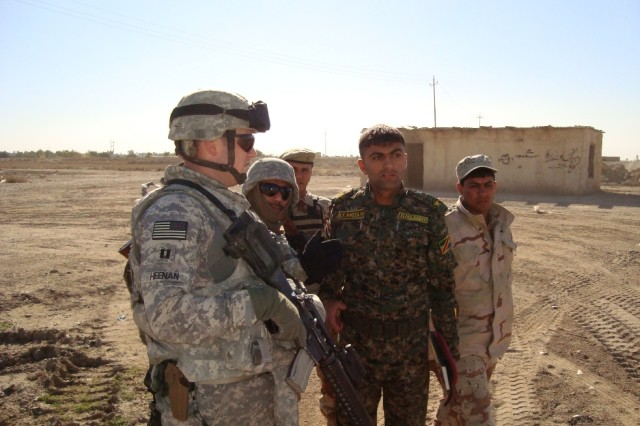 BAGHDAD - Capt. Sean Heenan (left), commander, Company A, 46th Engineer Combat Battalion (Heavy) discusses the scope of work with Iraqi engineers from the 6th Iraqi Army during a route sanitation mission in downtown Baghdad.