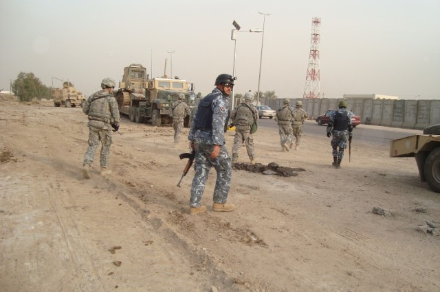 BAGHDAD - A joint security element composed of Soldiers from 2nd Battalion, 14th Cavalry Regiment, 2nd Brigade, 25th Infantry Division and the 6th Iraqi Army prepare to move into position to secure the roadways for route sanitation near the Muthana Airfield in downtown Baghdad.