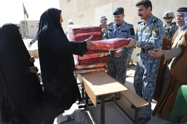 BAGHDAD - Iraqi Brig. Gen. Ali Ibraheem Dabown, commander of the 8th National Police Brigade, 2nd NP Division, gives a wool blanket to a woman during a humanitarian drive Feb. 4 at a school in the New Baghdad district of eastern Baghdad. More than 800 blankets were given to citizens of New Baghdad during the event. Paratroopers assigned to the 2nd Battalion, 505th Parachute Infantry Regiment, 3rd Brigade Combat Team, 82nd Airborne Division, Multi-National Division-Baghdad,  partnered with Iraqi Security Forces during the operation.