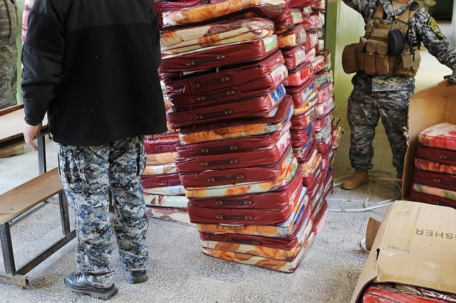 BAGHDAD, Iraq - National Police officers assigned to the 8th National Police Brigade, 2nd NP Division, stack wool blankets during a humanitarian drive Feb. 4 at a school in the New Baghdad district of eastern Baghdad. The is the second humanitarian drive held in the past two weeks by the 8th NP Bde and Paratroopers assigned to 2nd Battalion, 505th Parachute Infantry Regiment, 3rd Brigade Combat Team, 82nd Airborne Division, Multi-National Division-Baghdad. The two units plan to hold a third humanitarian event later this month.