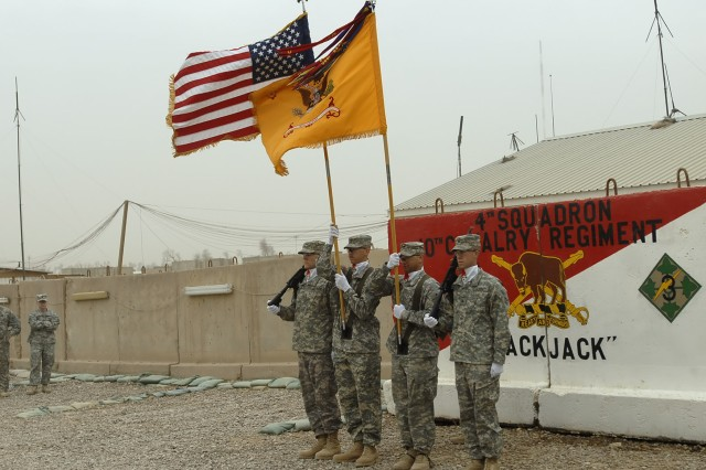 """BAGHDAD - Members of a flag detail with the 4th Squadron, 10th Cavalry Regiment """"Blackjack"""", attached to the 2nd Heavy Brigade Combat Team, 1st Infantry Division, Multi-National Division - Baghdad stand at the position of attention during their Transfer of Authority Ceremony with the 5th Sqdn. 4th Cav. Regt. """"Longknife"""",  2nd HBCT, 1st Inf. Div., MND-B. The hand-off will give the Longknife Squadron more battle space to cover."""
