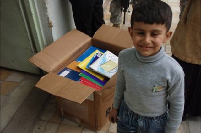 BAGHDAD - A student at the Abi Tammam Boys Primary School smiles while receiving school supplies Feb. 10 in the Karkh district of northwest Baghdad.  Soldiers from the 4th Battalion, 42nd Field Artillery Regiment, attached to the 2nd Heavy Brigade Combat Team, 1st Infantry Division, Multi-National Division-Baghdad, delivered donated supplies from numerous organizations and Families in the United States.