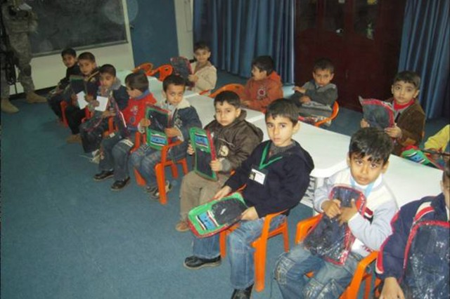 BAGHDAD - Students at the Abi Tammam Boys Primary School receive back packs from Multi-National Division-Baghdad Soldiers during a school supply delivery Feb. 10 in the Karkh district of northwest Baghdad.  The Soldiers, from the 4th Battalion, 42nd Field Artillery Regiment, attached to the 2nd Heavy Brigade Combat Team, 1st Infantry Div., surprised the school children with the well received supplies.