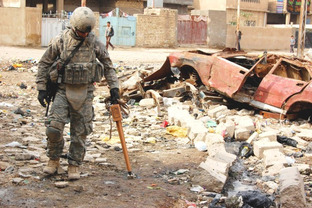 HUSSANIYAH, Iraq - Pfc. Matthew McMahon, an infantryman, with 1st Battalion, 27th Infantry Regiment, 2nd Stryker Brigade Combat Team, 25th Infantry Division, uses a metal detector to search for illegal weapons caches in northease Baghdad Feb. 9. McMahon, a native of Littleton, Colo., partnered with Al Salaam Iraqi Police officers during the combined operation focused on ridding the Hussaniyah Nahia of enemy weapons.