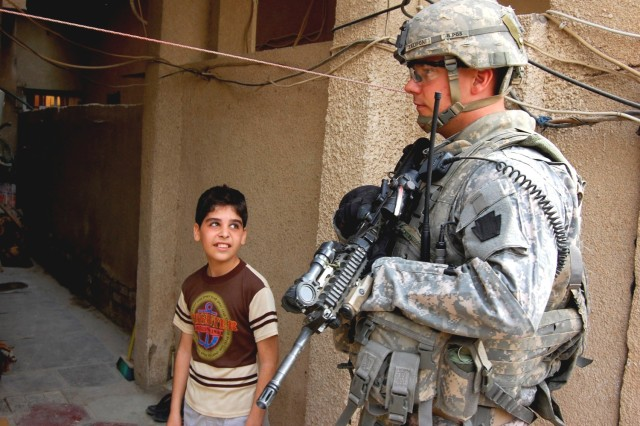 HUSSANIYAH, Iraq - Sgt. Aaron Zaliponi, an infantry squad leader, with 56th Stryker Brigade Combat Team, 28th Infantry Division, Pennsylvania Army National Guard, passes a young boy while searching for illegal weapons cache Feb. 9. Zalioponi, a native of Butler, Pa., partnered with Al Salaam Iraqi Police officers during the combined clearance operation.