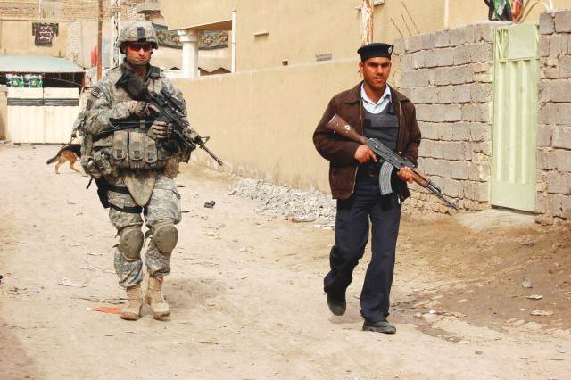 HUSSANIYAH, Iraq - Sgt. 1st Class Roger Young (left), infantry platoon sergeant, with 56th Stryker Brigade Combat Team, 28th Infantry Division, Pennsylvania Army National Guard, patrols side-by-side with an Al Salaam Iraqi Police officer Feb. 9.  Young, a native of Monaca, Pa., participated in the combined operation focused on removing illegal weapons caches from the Hussaniyah Nahia in northeastern Baghdad.