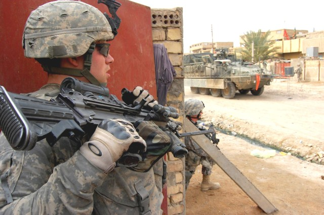 HUSSANIYAH, Iraq - Pfc. Jeffrey Arnold, an infantryman, assigned to 1st Battalion, 27th Infantry Regiment, 2nd Stryker Brigade Combat Team, 25th Infantry Division, maintains security at the entrance of a house suspected of storing illegal weapons Feb. 9, while on a joint Iraqi Security Force operation in northeast Baghdad.  Arnold, a native of Cheney, Wash., partnered with Al Salaam Iraqi Police officers to clear and disrupt insurgent networks and weapons cache in and around the Hussaniyah Nahia.