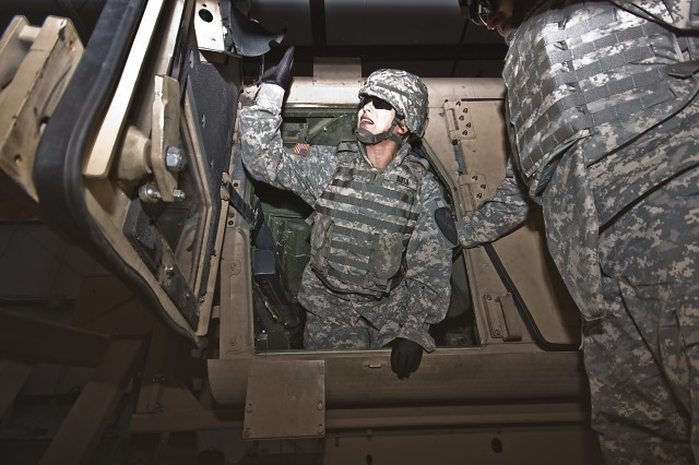 After flipping a couple of times, El Paso, Texas, native 2nd Lt. Nora Soto, the strength manager for the 1st Air Cavalry Brigade, 1st Cavalry Division, climbs out of the overturned HMMWV Egress Assistance Trainer with a little help from Chyenne, Wyo., native Maj. Bryan Woodcock, the S-2 officer in charge for 1st ACB, during rollover training at Fort Hood, Texas, Feb. 9. The HEAT class is meant to familiarize Soldiers with the feeling of being flipped in a humvee so that they are better equipped with skills to get out quickly and safely, said Shreveport, La., native Master Sgt. Blake Kennedy, the fires operations sergeant, for 1st ACB.