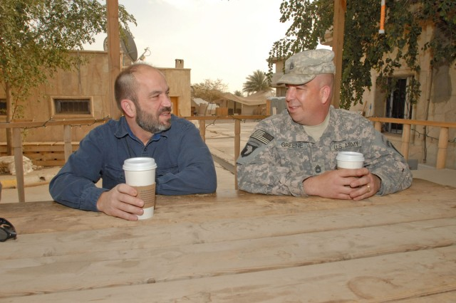 Robert Greene, Science Applications International Corporation, database administrator (left) and his brother, Sgt. 1st Class Daniel Greene, Headquarters and Headquarters Detachment, operations, 10th Mountain Division, operations noncommissioned officer-in-charge have grown closer through their time together in Iraq. The brothers spend time together drinking coffee, having dinner and reminiscing about their childhood.