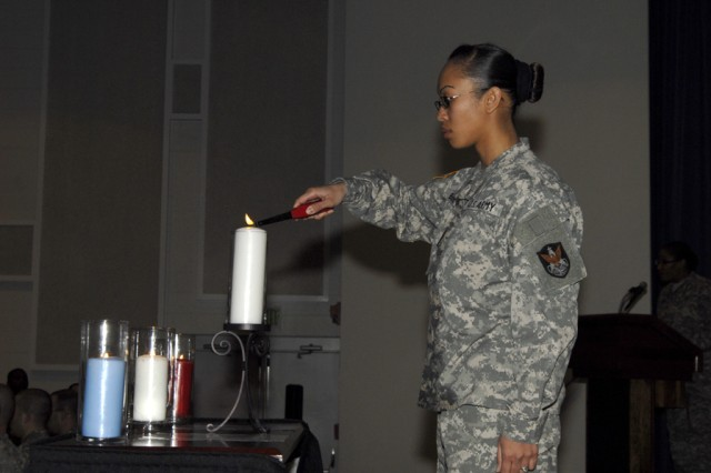 Sgt. Dianalou R. Boone from HHC, 1st Space Brigade, performs the closing portion of the 1st Space Brigade NCO Induction Ceremony with the lighting of the Eternal Flame. This honor goes to the youngest inductee.