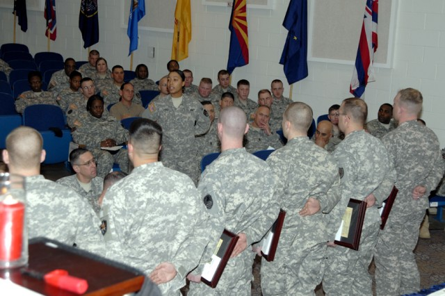 (Center) Pfc. Kaila Lord gives a Soldier's Request to the newly inducted NCOs before her as part of the 2009 1st Space Brigade NCO Induction Ceremony conducted at the Peterson Air Force Base Auditorium on Feb. 5.