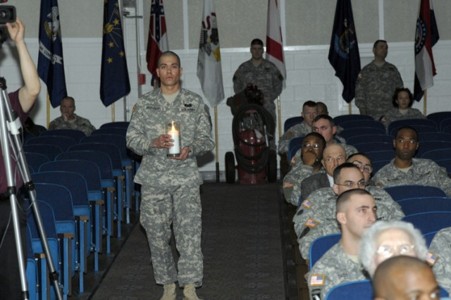 Staff Sgt. David Rodgers from the 1st Space Battalion brings forth the White Candle during the Lighting of the NCO Spirits portion of the 2009 1st Space Brigade NCO Induction Ceremony conducted at the Peterson Air Force Base Auditorium on Feb. 5.