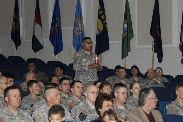 Sgt. Martin Santistevan from HHC, 1st Space Brigade, brings forth the Red Candle during the Lighting of the NCO Spirits portion of the 2009 1st Space Brigade NCO Induction Ceremony conducted at the Peterson Air Force Base Auditorium on Feb. 5.