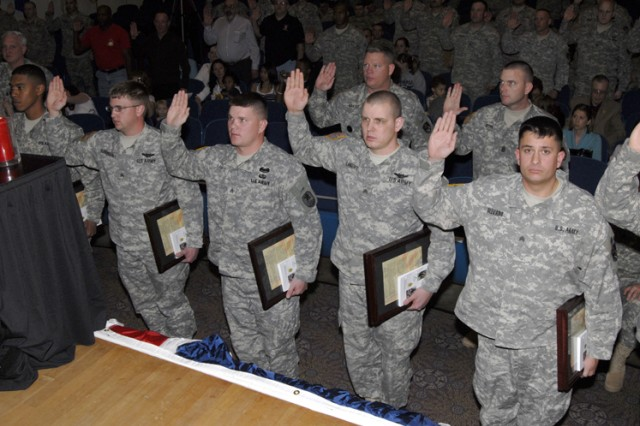 (Left to Right) Sgt. Christopher Kaufmann, Sgt. Brandon LaForce, Sgt. Michael Landry, and Sgt. Matthew Olevano all receive the Charge of the Noncommissioned Officer from 1st Space Brigade Command Sgt. Maj. Kevin McGovern as part of the 2009 1st Space Brigade NCO Induction Ceremony conducted at the Peterson Air Force Base Auditorium on Feb. 5.