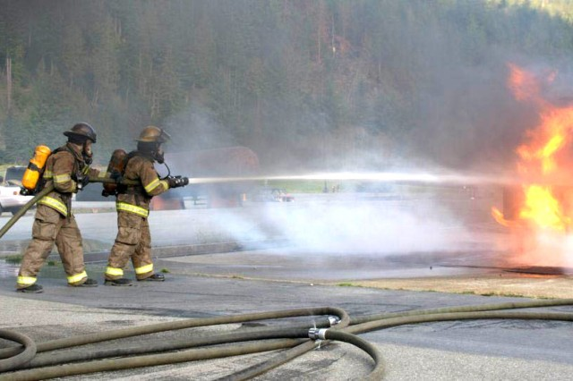 Sergeant Chad Weathers and Spc. Justin Hulslander of 402nd Brigade Support Battalion hose down a fire at the Washington State Fire Academy in North Bend, Wash.