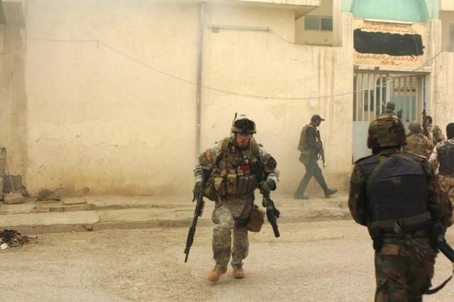 Staff Sgt. Stuart Fowler, a 2nd Platoon, Company A, 5th Battalion, 20th Infantry Regiment sniper, runs across a Baqubah street to his next firing position.