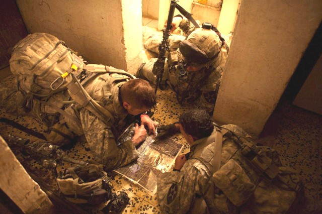 A 5th Battalion, 20th Infantry Regiment platoon leader gathers his squad leaders to plan their next move during clearing operations to drive insurgents out of Baqubah June 20, 2007.