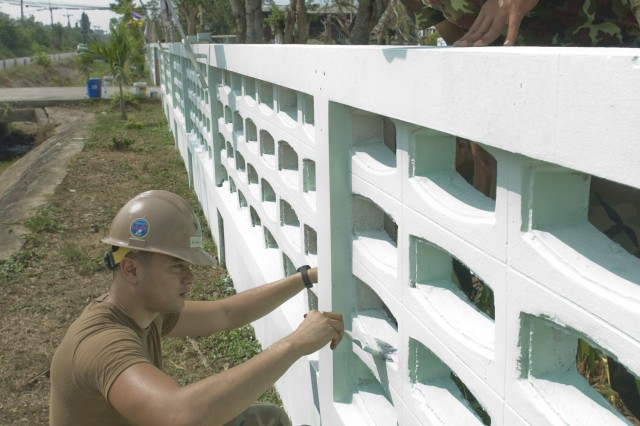 Utaphao, Thailand (February 12, 2009) - Construction Mechanic 3rd Class (SCW) Jeff Schroeder from Beatty, N.V., left, assigned to Combat Logistics Regiment Three of the 31st Marine Expeditionary Unit, works alongside Royal Thai Marines to paint the fence at Banklong Sai Elementary School as part of a community relations project during Exercise Cobra Gold 2009. Cobra Gold is an annual Kingdom of Thailand and U.S. co-sponsored military exercise designed to train U.S. and partner Asian-Pacific forces. The exercise will include humanitarian projects with participants from Indonesia, Japan, Singapore, Thailand and the U.S. The U.S. will also engage with Thai military forces in a field training exercise to promote familiarity with and cohesion between these partner nations' military forces. CG 09 provides a multinational environment to strengthen the bonds between the Thai community and partner militaries.