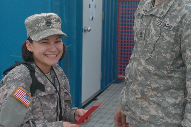"Staff Sgt. Richard Abrue and Staff Sgt. Gabriela Abrue, spouses and fellow soldiers of the 143d Expeditionary Sustainment Command, exchange cards on Valentine's Day before their temporary separation.  Gabriela, a noncommissioned officer in support operations, left Feb. 14 with the advance party of the 143d ESC, which has been dispatched to Afghanistan to support the buildup there. Richard, an NCO in the intelligence section, is scheduled to leave with the main body later this month. The couple has been married for six years and have two children, Leah—5 and Macho—4, who will live with close family members in Australia, while their parents are gone. Richard said that working in the same unit with his wife is ""great for support."""