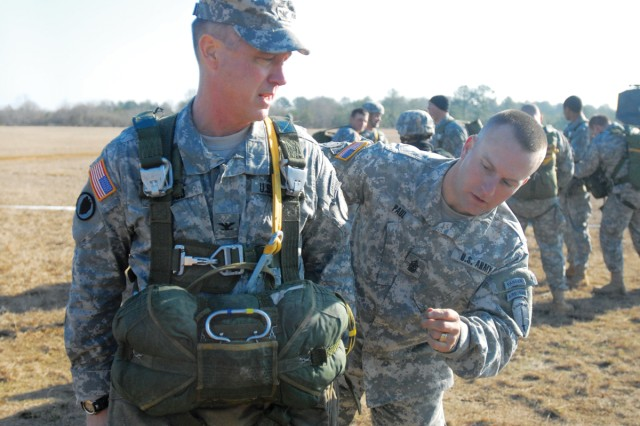 """""""I'm truly going to miss the professionalism of the senior NCOs on this post. They're second to none,"""" said COL Jerry Wood, pictured here with SGM Billy Paul, the SACG sergeant major, during a gear check before Wood's final jump on Fryar Field. Last week, Wood left his position as the National Guard's special assistant to the commanding general to become the chief of staff at the Office of the Deputy Commanding General, Army National Guard, at Fort Monroe, Va."""