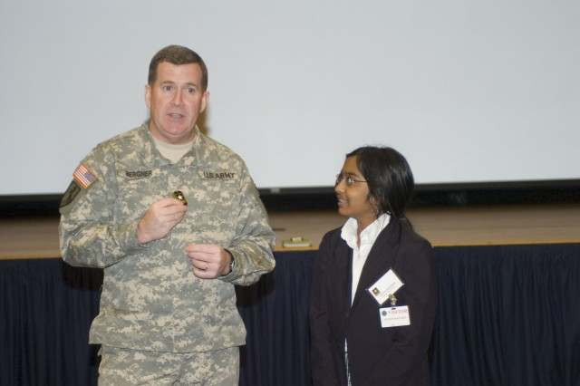 Army Chief of Public Affairs Maj. Gen. Kevin Bergner presents Episcopal School of Dallas student Lakshmi Uppalapati with a coin for answering a question correctly.