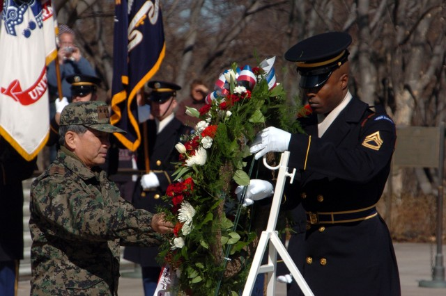 Sgt. 1st Class Alfred Lanier, the sergeant of the Guard at the Tomb of the Unknown Soldier in Arlington National Cemetery, assists Gen. Choung-Bin Lim, the Chief of Staff of the Army for the Republic of Korea.