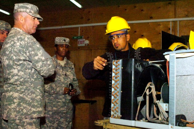 "Multi-National Force - Iraq Command Sgt. Maj. Lawrence K. Wilson (left), and Command Sgt. Maj. Valerie Greene, command sgt. maj., 25th Special Troops Battalion, 25th Infantry Division (center), supervise an Iraqi man as he adjusts wiring on his latest project at the Iraqi Based Industrial Zone at the Iraqi Based Industrial Zone on Contingency Operating Base Speicher, near Tikrit, Iraq, Feb. 17. ""At the rate these men are learning we will be out of a job soon,"" said Wilson. (U.S. Army photo by Pfc. Jesus J. Aranda, Task Force Lightning Public Affairs)"