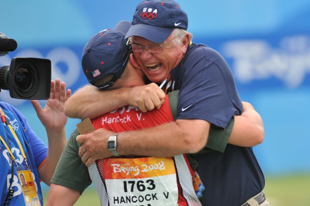 Team USA shotgun coach Lloyd Woodhouse, a retired Airman, hugs Pfc. Vincent Hancock after he wins the Olympic gold medal in men's skeet, Aug. 16, at the Beijing Shooting Range.