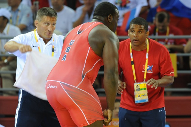 Staff Sgt. Shon Lewis (right) and Marine Corps Maj. Jay Antonelli (left) coach Staff Sgt. Dremiel Byers to a 4-0, 1-1, 1-1 victory over China's Deli Liu in the second round of the Olympic Greco-Roman tournament.