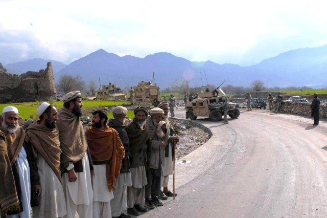 Villagers wait for the governor of Afghanistan's Konar province to arrive for the official opening of a paved road in the province's Deywagal Valley, Feb. 5, 2009. The seven-mile road was completed after two years of work, offering Afghans better access to hospitals, schools and markets.