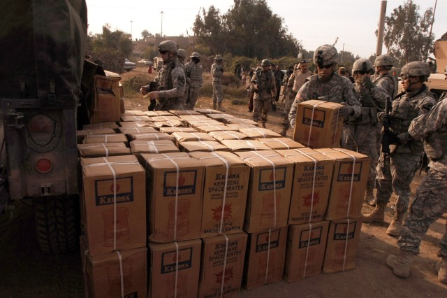 Spc. Gregory Clarke, 3rd Battalion, 82nd Field Artillery Regiment, 2nd Brigade Combat Team, 1st Cavalry Division, stacks boxes of kerosene heaters for distribution during a humanitarian aid mission at the Quds Camp in central Baghdad's Janeen neighborhood.
